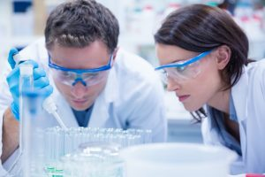 Optimized-chemist-team-working-with-pipette-and-test-tube-in-PZ698GZ